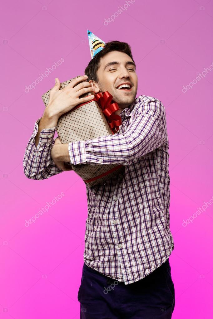 Happy Young Handsome Man Embracing Birthday Gift In Box Over Purple Background Copy Space