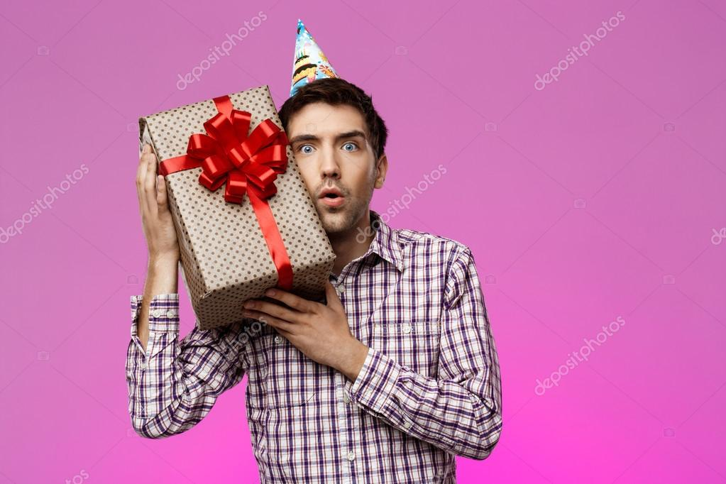 Happy Young Handsome Man Holding Birthday Gift In Box Over Purple Background Copy Space Foto Von Nkkravchenkogmail