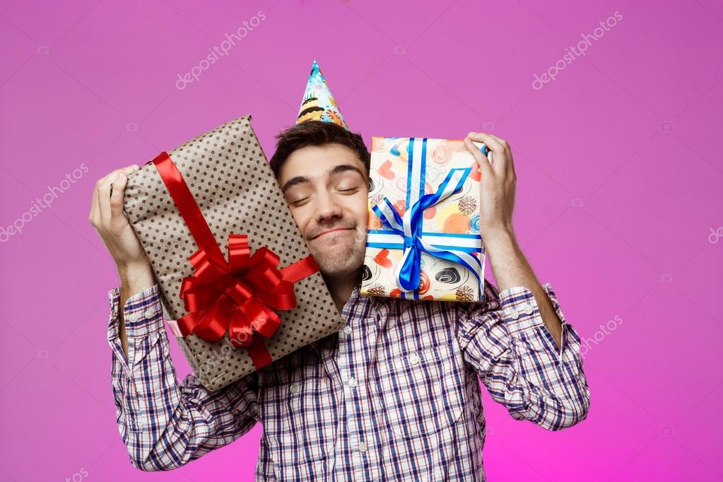 Happy Young Man Holding Birthday Gifts In Boxes Over Purple Background Copy Space