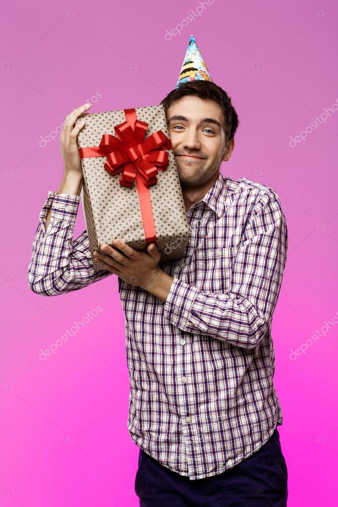 Happy Young Man Embracing Birthday Gift In Box Over Purple Background Stock Photo
