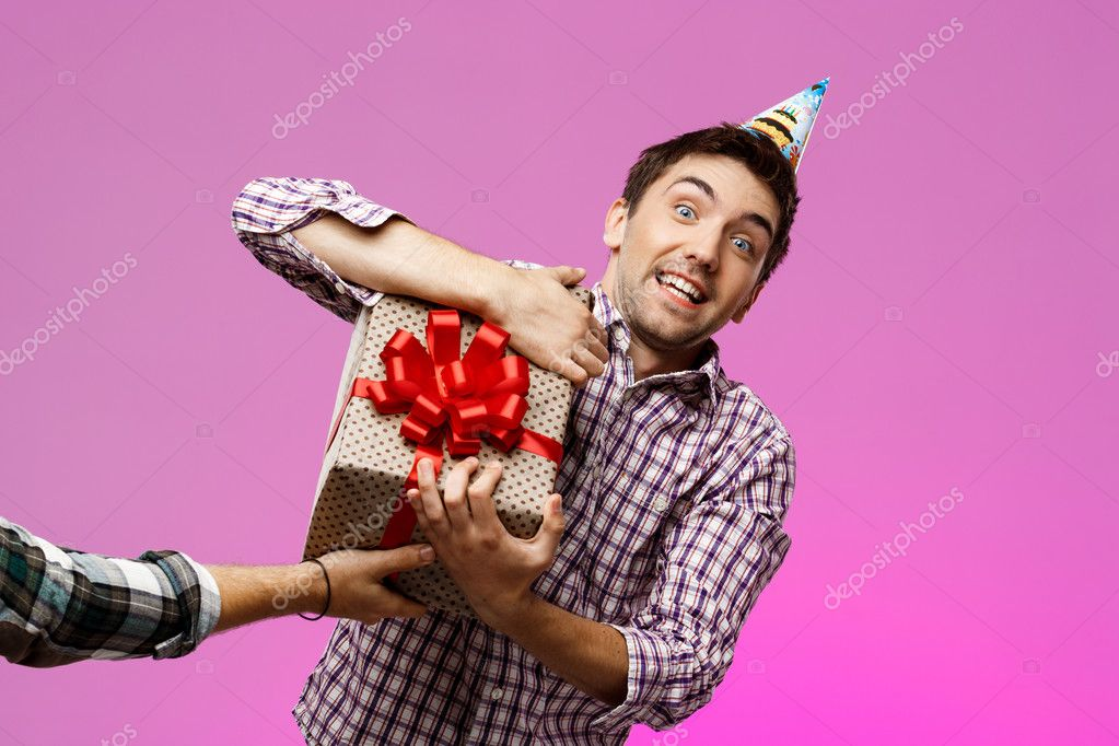 Man tearing out birthday gift in box over purple background.