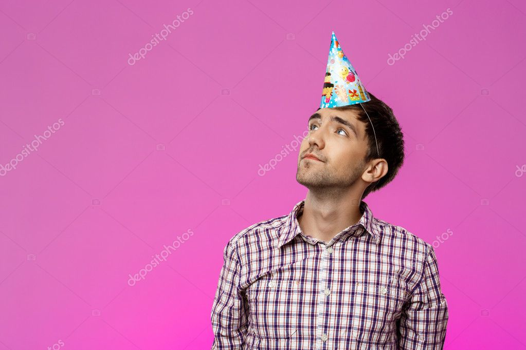 Young man wearing fake glasses over purple background. Birthday party.