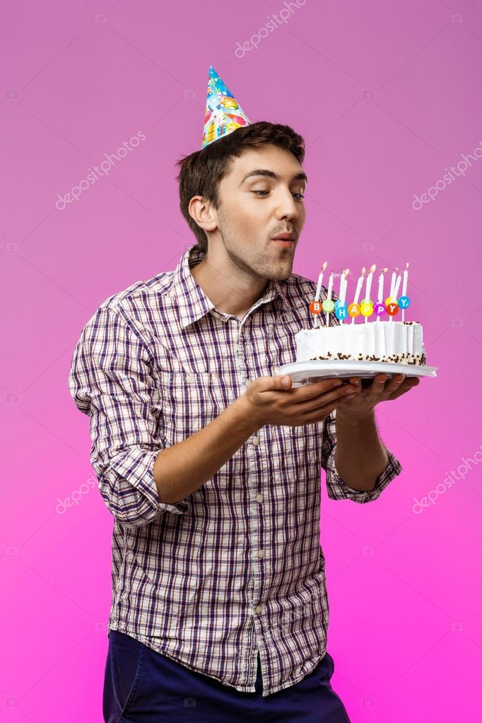 Man blowing out candles on birthday cake over purple background.