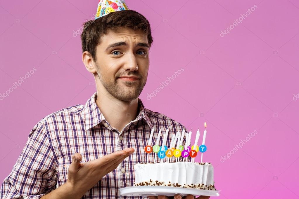 Upset man holding birthday cake with one not blow out candle.