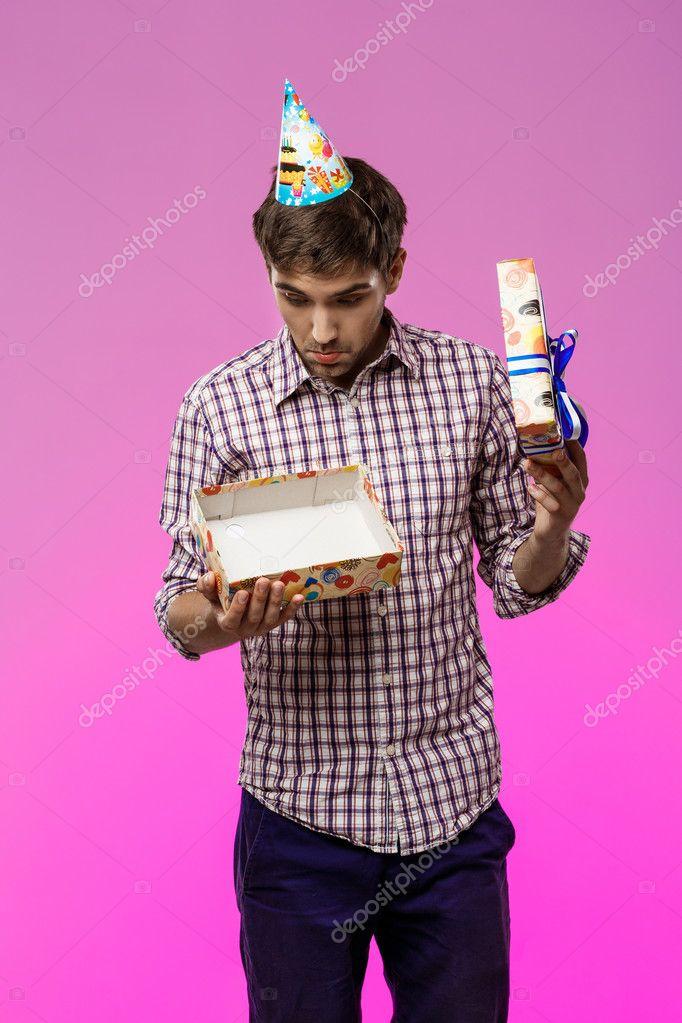 Hombre guapo joven abriendo el regalo de cumpleaños sobre fondo ...