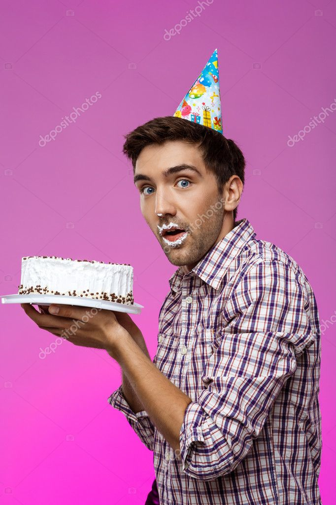 Man with cake on lips over purple background. Birthday party.