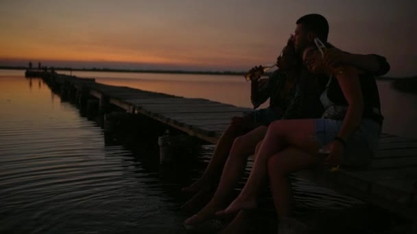 Friends sitting at pier embracing smiling speaking at sunrise Slow motion