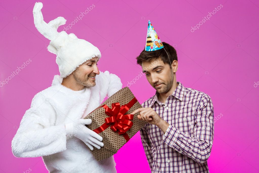 Rabbit giving birthday gift to drunk man over purple background.