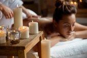 Krásná mladá dívka relaxaci ve spa salonu. Zaměřit se na svíčky