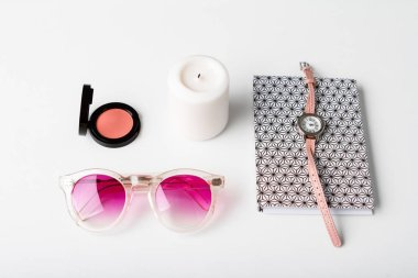 Decorative cosmetics accessories wristwatch candle and sunglasses over white background.