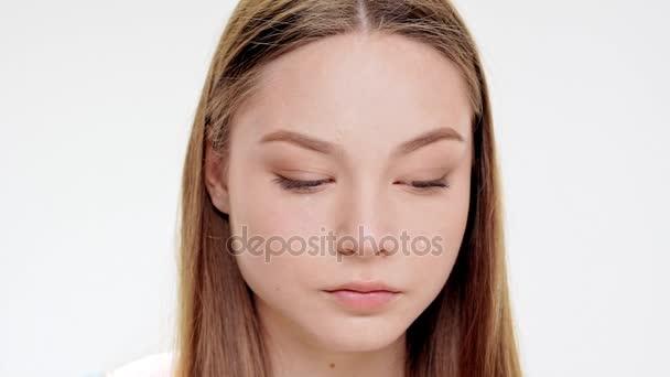 Smutně krásná mladá dívka nad plačící bílým pozadím. Zpomalený pohyb