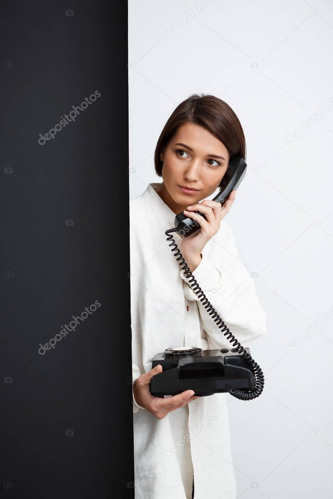 Girl speaking on old phone over black and white background.