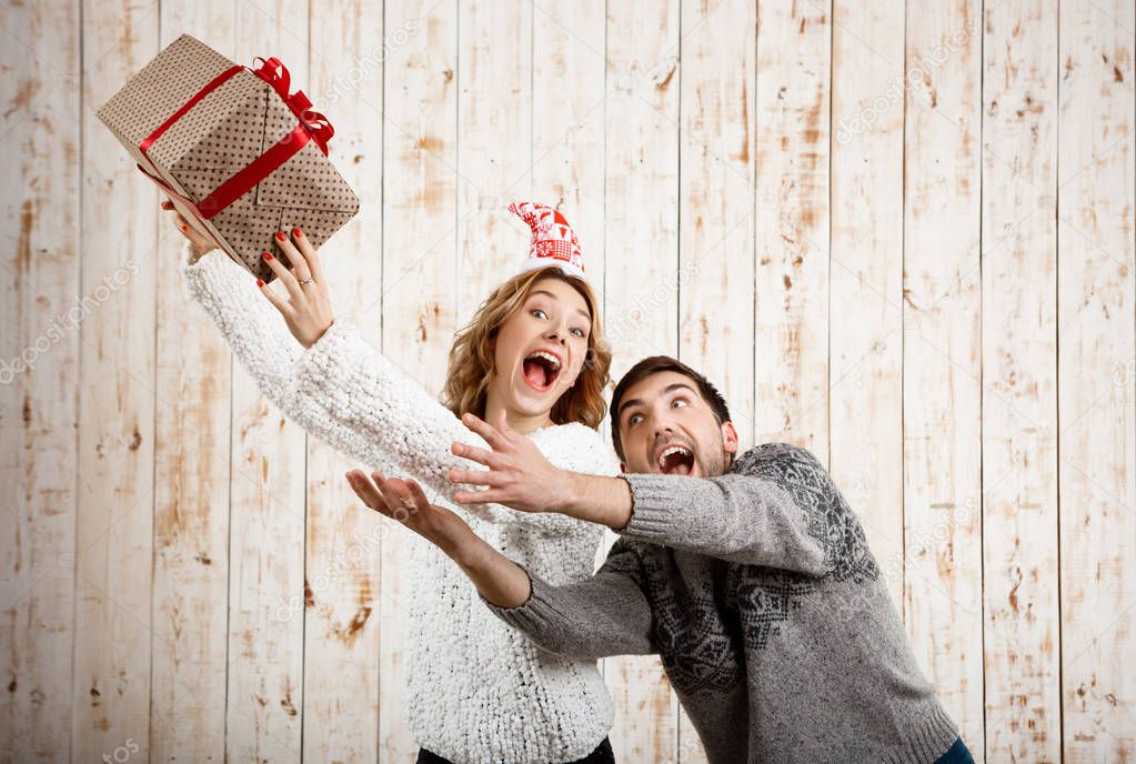 Young beautiful couple fighting for  christmas gift over wooden background.
