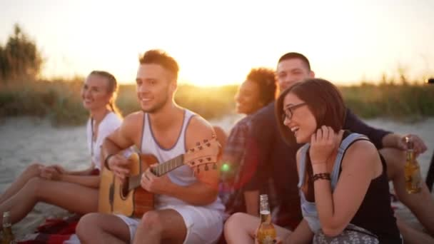 Company of friends rejoicing laughing resting at beach at sunrise Slow motion