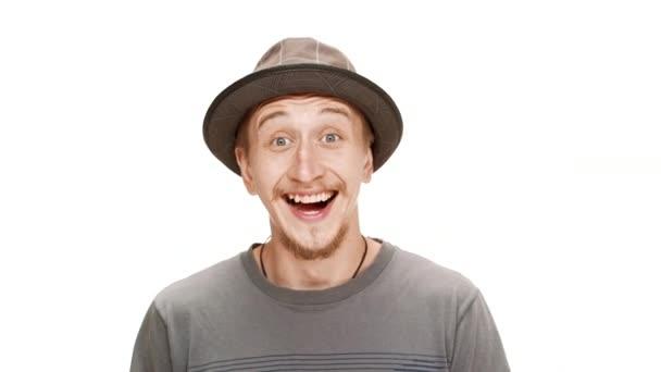 Meglepett, jóképű fiatalember mosolygott, örült mint fehér háttér kalapban.