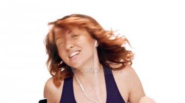 Krásná mladá dívka poslech hudby ve sluchátkách, tanec, zpěv nad bílým pozadím