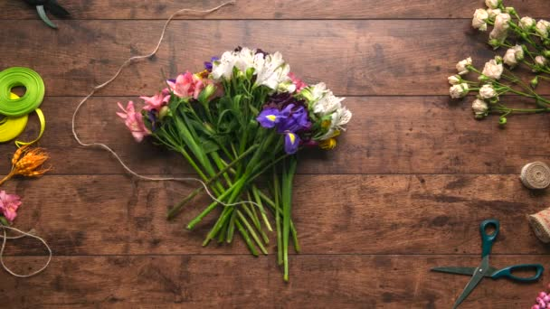 Creation of bouquet from flowers with different colours Wooden background Stop motion animation