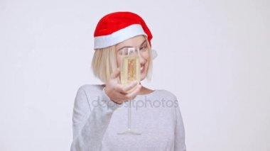 Krásná mladá blondýnka dívka v vánoční čepice drží sklenku vína topinkovače mrkání ukazuje palec nad bílým pozadím