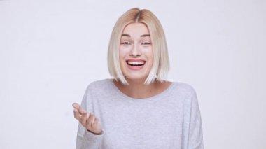 Mladá krásná blonďatá dívka s úsměvem překvapil vzrušený zobrazeno palce nahoru nad bílým pozadím Zpomalený pohyb