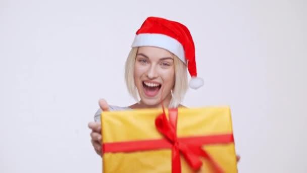 Nejlepší okamžik svátků Yooung hezká blondýnka dívka v klobouku vánoční dárek velké žluté krabice bílé pozadí