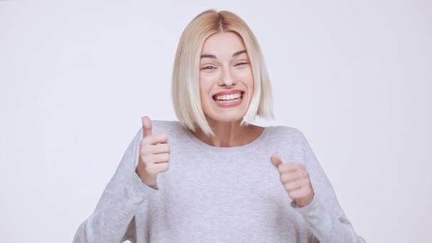 Young beautiful blonde girl smiling surprised excited showing thumbs up over white background Slow motion
