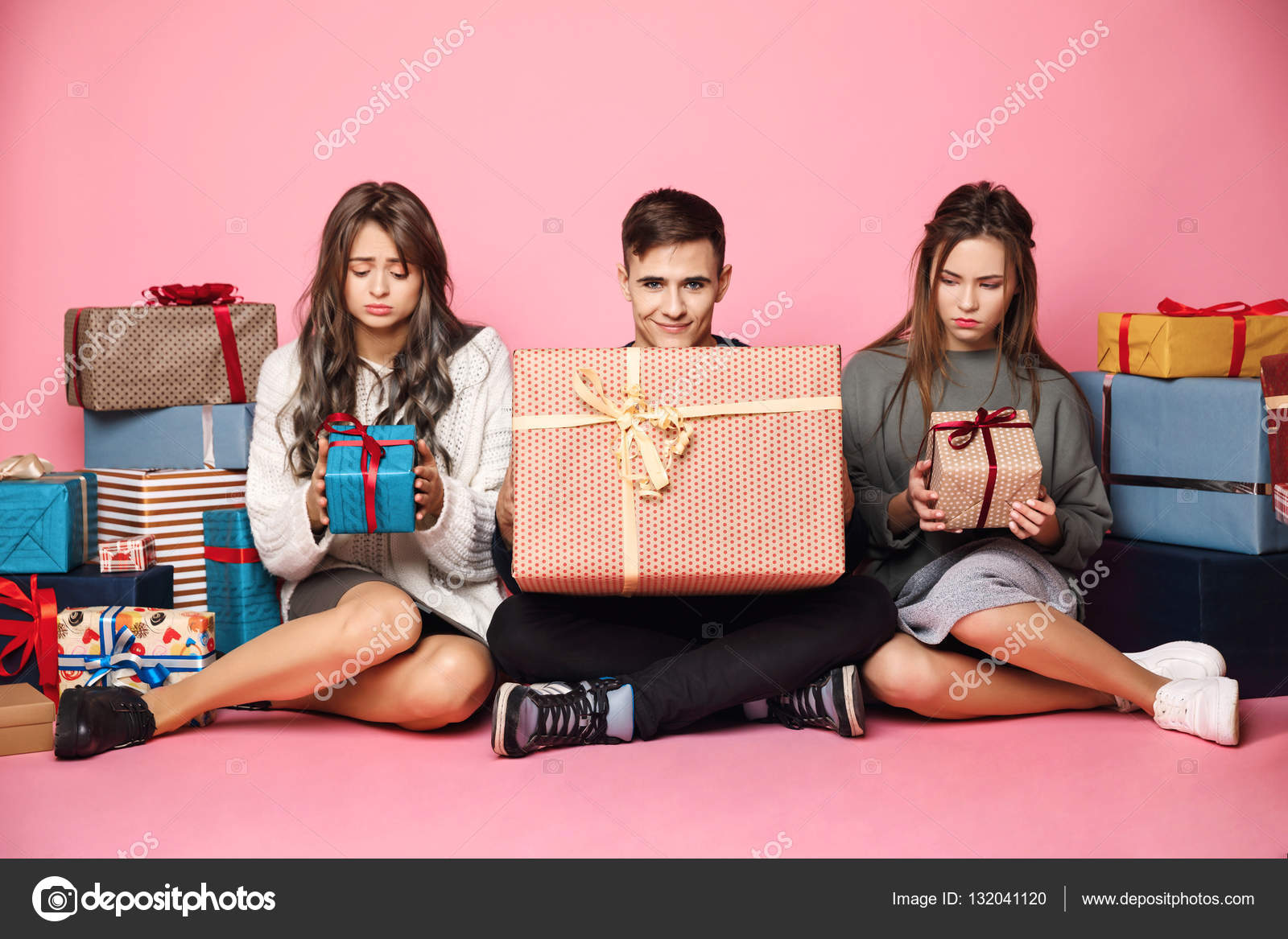 Freunde sitzen unter Weihnachtsgeschenke. Mann hält große box ...