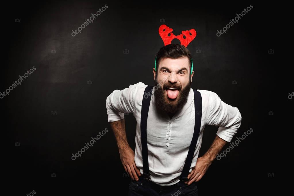 Man in fake deer horns showing tongue over black background.
