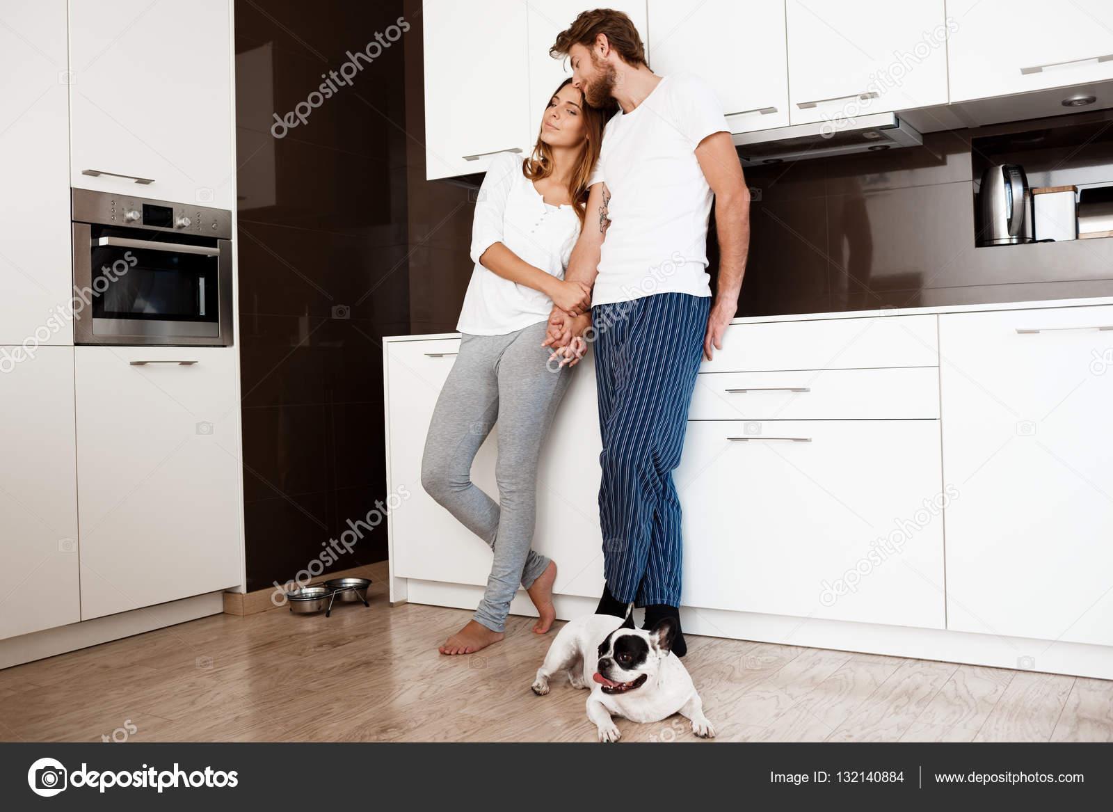 Joven pareja hermosa sonriendo de pie en la cocina con perro pug ...