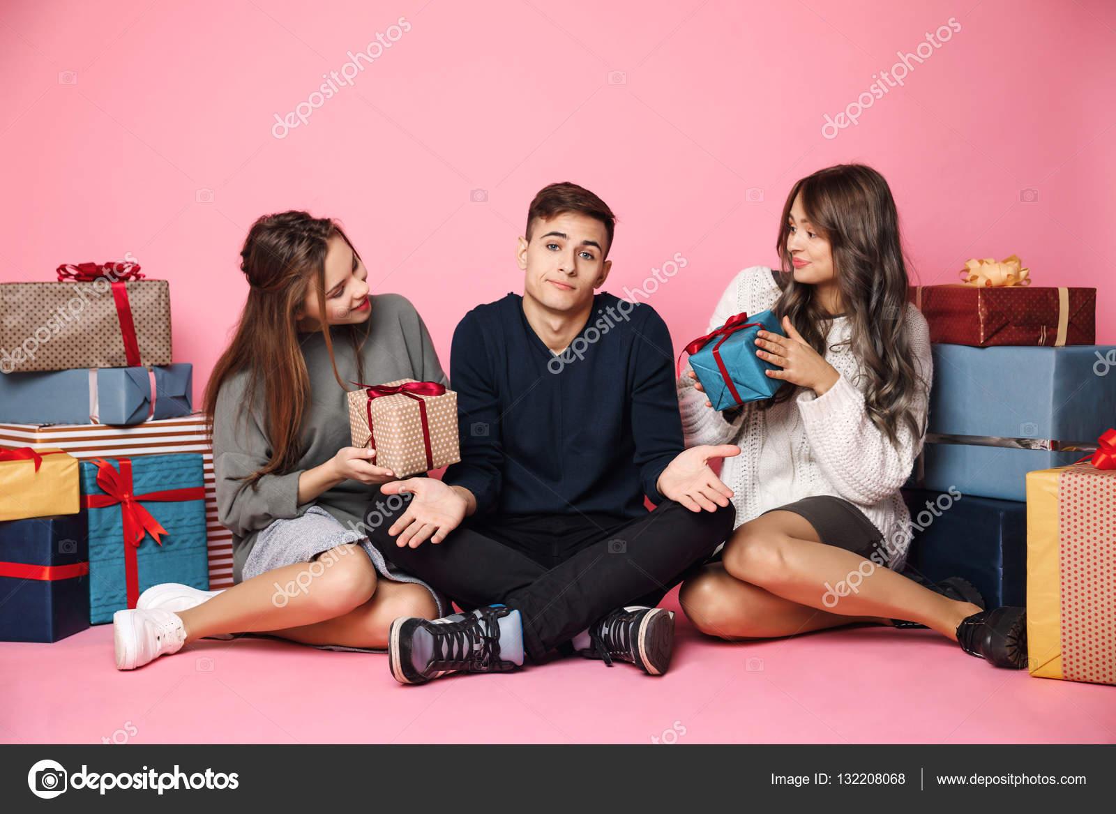 Freunde sitzen unter Weihnachtsgeschenke über rosa Hintergrund. Mann ...
