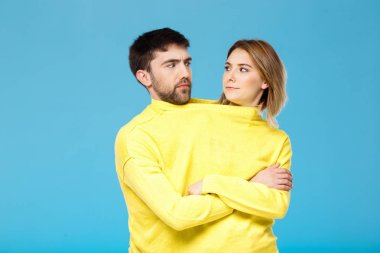 Couple in yellow sweater posing with crossed arms over blue background.