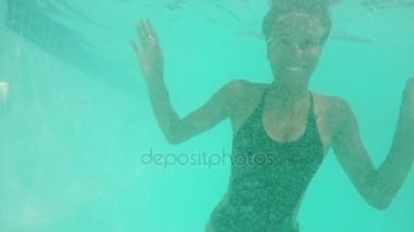 Cute African American female in black swimsuit diving in pool smiling laughing. Close up underwater footage in slowmotion