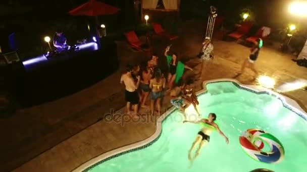 Night pool party. DJ playing music people drinking laughing dancing in swimsuits. Tilt view from drone