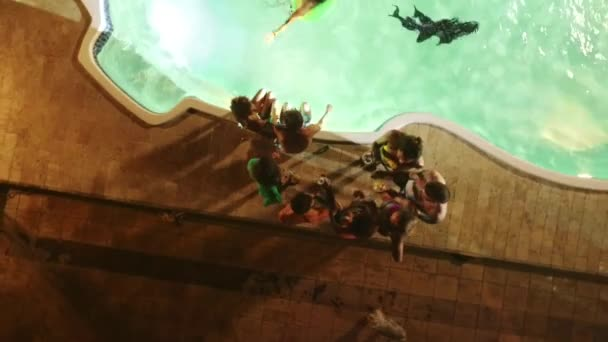 Pool party at night with group of people laughing smiling dancing talking and DJ. Counterclockwise footage from drone