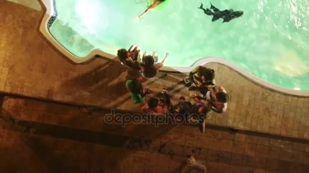 Pool-Party in der Nacht mit der Gruppe von Menschen lachen, Lächeln, tanzen, reden und Dj. entgegen dem Uhrzeigersinn Aufnahmen von Drohne