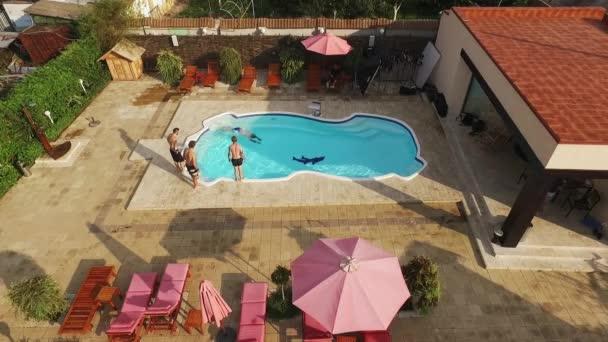 Čtyři belochu polonahá stojící vedle bazénu skákat do modré vody. Pohled shora z dron v slowmotion