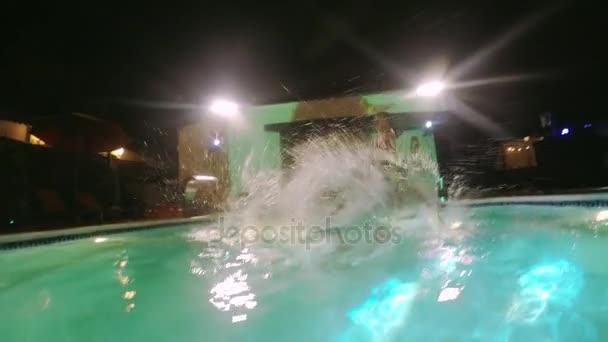 Gruppe von vier Freunden Sprung ins Schwimmbad bei Nacht. Unterwasseraufnahmen in slowmotion