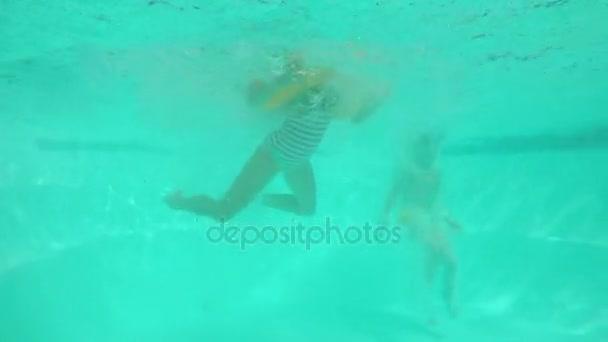 Vier Kinder springen in Pool mit laufen schwimmen lächelnd mit aufblasbaren Schläuchen. Unterwasseraufnahmen in slowmotion