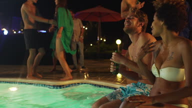 Handsome topless Caucasian guy with light beard and beer speaking with African American female in white swimsuit laughing smiling sitting at night pool party. In slowmotion