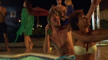Cute African American female sitting close to Caucasian male with light beard and beer playing with beachball with dancing people on background at night pool party. In slowmotion