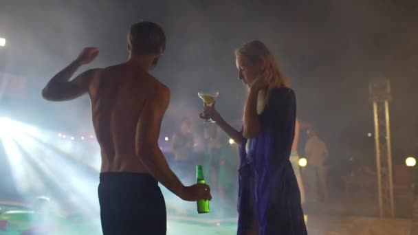 Topless Caucasian male with beard holding bear dancing in front of blonde female with cocktail at night pool party in glow of spotlights. In slowmotion