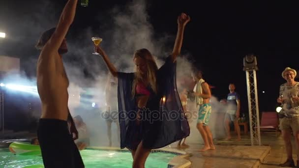 Topless Caucasian male with dark beard and beer dancing with blonde female with cocktail at night pool party with people on background. In slowmotion
