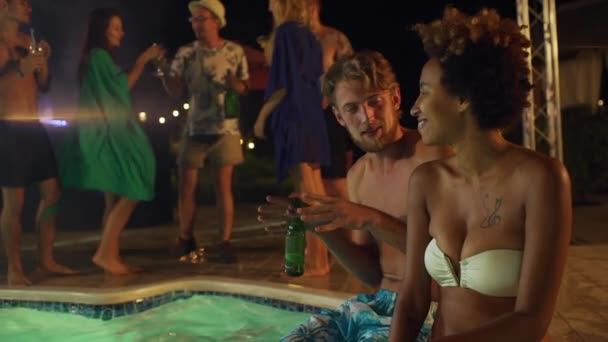 Caucasian topless male with light beard drinking beer and talking to African American female in white swimsuit laughing smiling in slowmotion at night pool party
