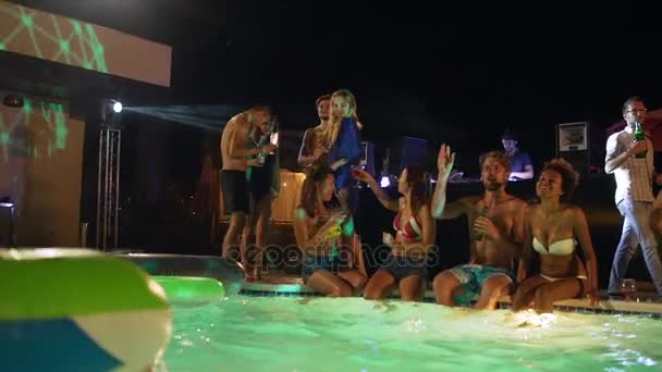 Group of beautiful males and females sitting standing at night pool party drinking cocktails playing beachball smiling laughing talking in slowmotion