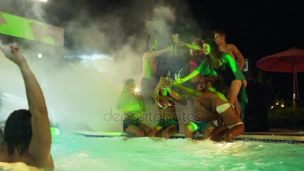 Beautiful males and females sitting standing at night pool party drinking cocktails in glow of green spotlights and smoke talking laughing smiling in slowmotion