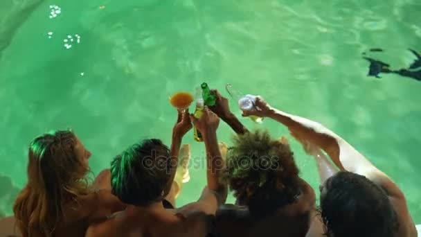 Four males and females sitting at pool with legs in water drinking beer and cocktails in slowmotion. Top view at night pool party