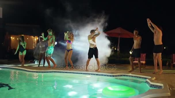 Nahoře bez kavkazských mužů a žen v plavkách taneční skákání v bazénu na party venku v noci. V slowmotion