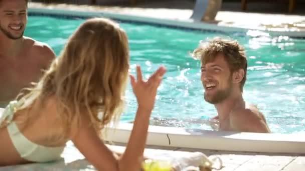 Junge schöne blonde Kaukasische Frau am flirten mit zwei topless Männchen im Pool Lounge liegen. In slowmotion