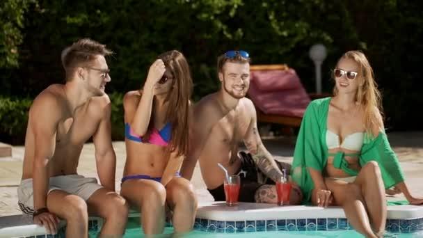 Kavkazské krásné dvoje sedí u bazénu pití koktejlů mluví s úsměvem. V slowmotion