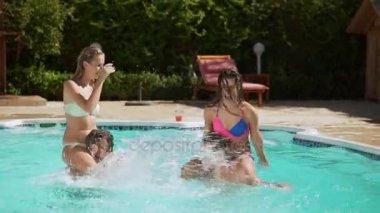 Két vonzó kaukázusi nő ül a két férfi nyakát fröccsenő víz medence játék. A Slow Motion
