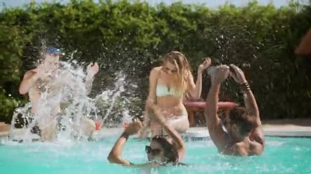 Two beautiful females and two handsome males actively splashing water on each other in pool. In slowmotion